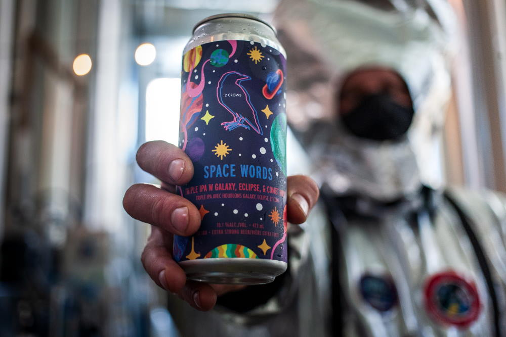 An astronaut holds our Space Words beer towards the camera where the focus is on the label.