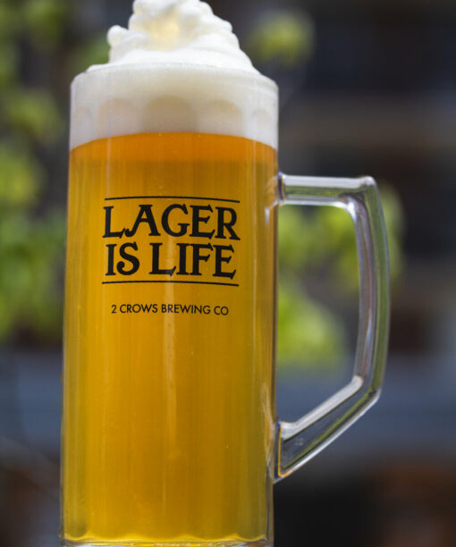 A tall stein like glass is full of our Letna Lager with a generous amount of foam sits on top of the beer stacked higher than the glass.
